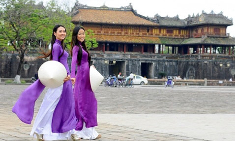 Girls walk gracefully in the Hue traditional Ao dai