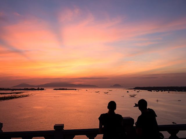 Witness sunset views from cua dai bridge at Vietnam holiday packages